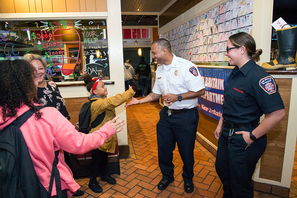 09/25/19 Wesley Bunnell | StaffrrTip a Firefighter took pace at Chili's in New Britain on Wednesday night. The event raised money for the city 's partnership with the community foundation regarding the new disaster relief program. Fire Chief Raul Ortiz greets Kasiyah Ocasio, age 10, and her family at the entrance.