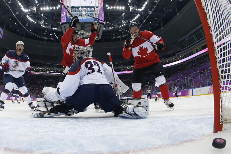 . Canada\'s Jamie Benn (C) celebrates with teammate Canada\'s Corey Perry (R) after scoring against US goalkeeper Jonathan Quick during the Men\'s Ice Hockey Semifinals USA vs Canada at the Bolshoy Ice Dome during the Sochi Winter Olympics on February 21, 2014.   JULIO CORTEZ/AFP/Getty Images