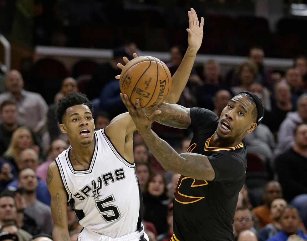 . Cleveland Cavaliers\' Iman Shumpert, right, grabs a rebound ahead of San Antonio Spurs\' Dejounte Murray (5) in the first half of an NBA basketball game, Saturday, Jan. 21, 2017, in Cleveland. (AP Photo/Tony Dejak)