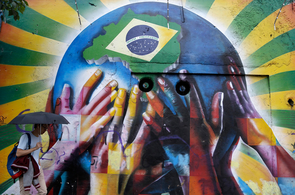 . A pedestrian passes a graffiti depicting human hands holding the earth with the Brazilian flag in Sao Paulo, Brazil, on Tuesday, June 10, 2014. The World Cup is set to open on June 12 with Brazil facing Croatia in Sao Paulo. (AP Photo/Thanassis Stavrakis)