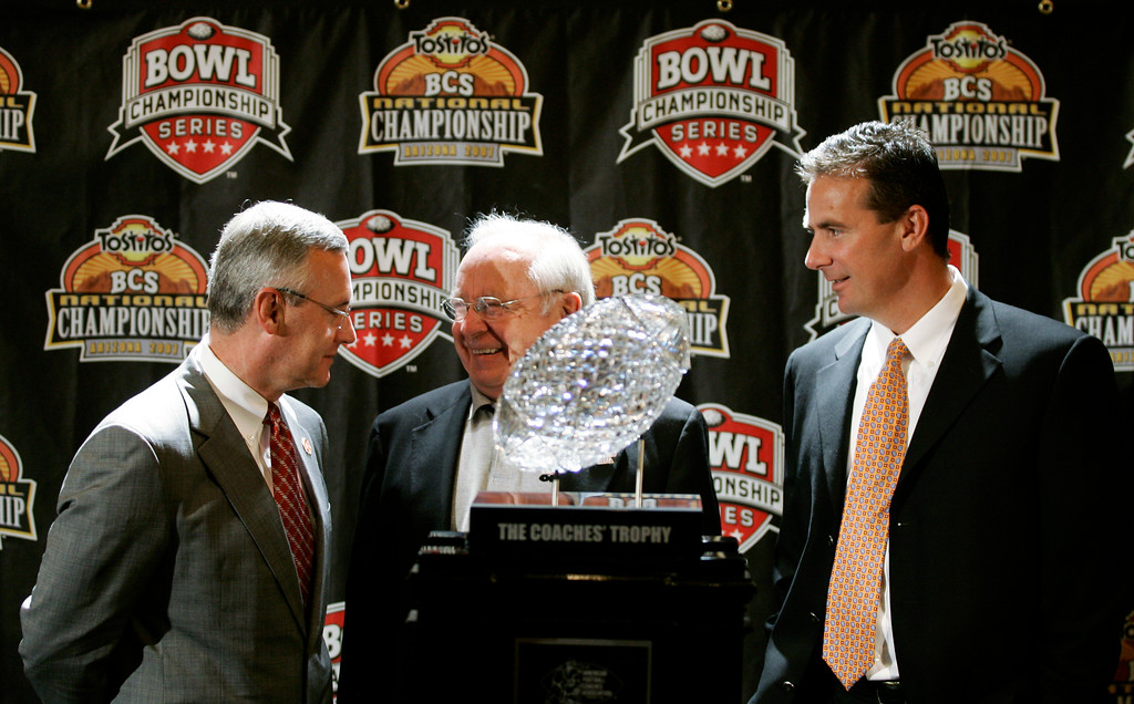 . Ohio State head coach Jim Tressel, left, and Florida head coach Urban Meyer, right, are joined by former Ohio State coach Earle Bruce, center, as they stand with the BCS college football championship trophy Sunday, Jan. 7, 2007, in Scottsdale, Ariz. Florida will face Ohio State Monday in the BCS college football championship game. (AP Photo/Ted S. Warren)