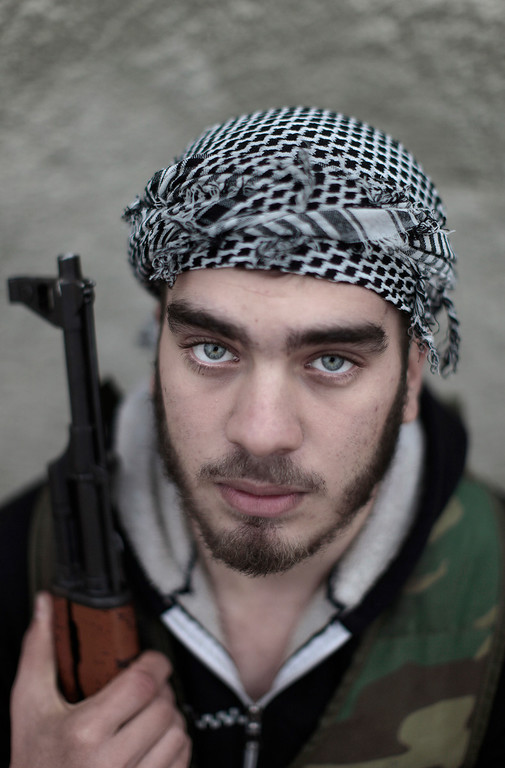 . In this Monday, Dec. 17, 2012 file photo, Syrian rebel fighter, Tariq, no last name given, 19, a former student, poses for a picture, following a training session in Maarret Ikhwan, near Idlib, Syria. More than two years into Syria\'s civil war, the once highly-centralized authoritarian state has effectively split into three distinct parts, each boasting its own flags, security agencies and judicial system. (AP Photo/Muhammed Muheisen)
