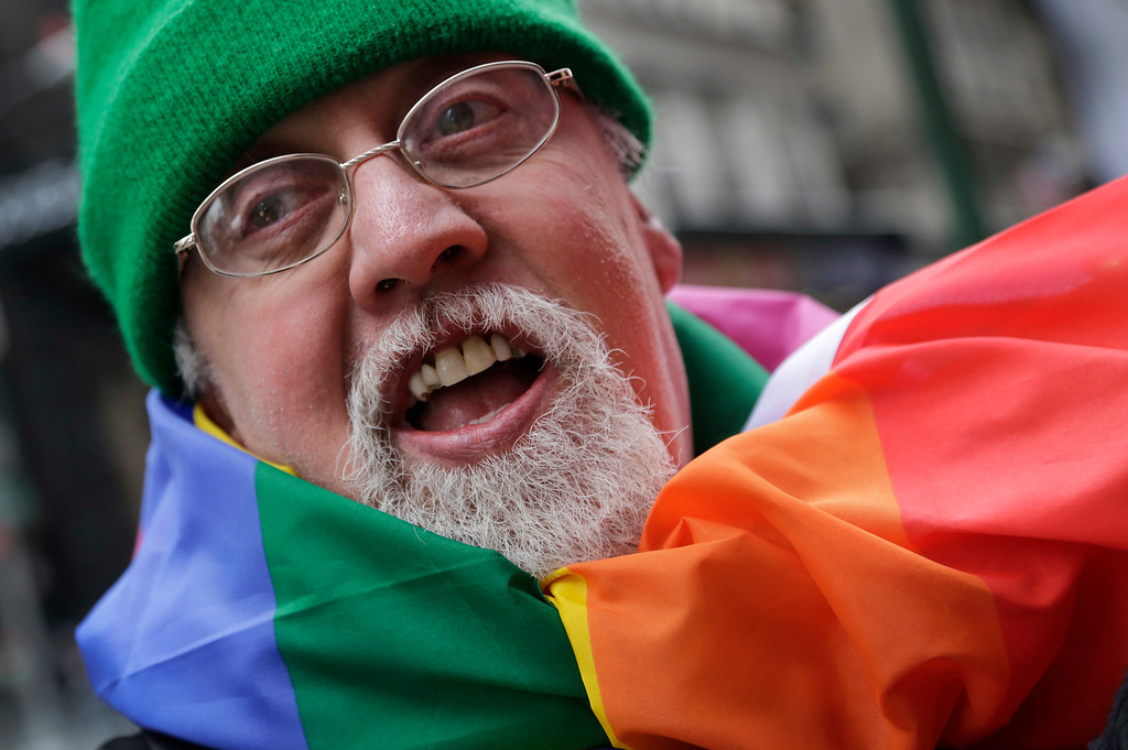 . FILE - In this Monday, March 17, 2014 file photo, artist Gilbert Baker, designer of the Rainbow Flag, is draped with the flag while protesting at the St. Patrick\'s Day parade in New York. Baker, creator of the flag that has become a widely recognized symbol of gay rights, has died at age 65. His death was reported Friday, March 31, 2017 to the New York City medical examiner�s office. (AP Photo/Mark Lennihan)