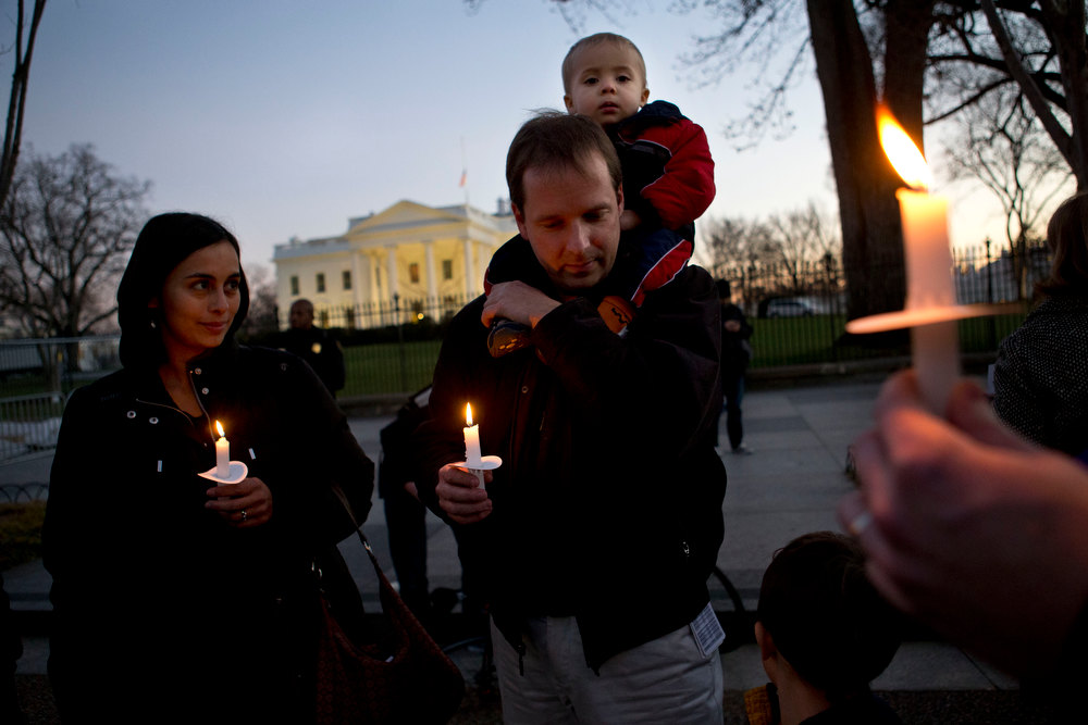 Description of . Next to his wife wife Fabiola Cordova, left, Chris Homan of Bethesda, Md., holds his son Leo, 2, on his shoulders while attending a candlelight vigil in front of the White House in Washington, Friday, Dec. 14, 2012, after a school shooting at Sandy Hook Elementary School in Newtown, Ct. (AP Photo/Jacquelyn Martin)