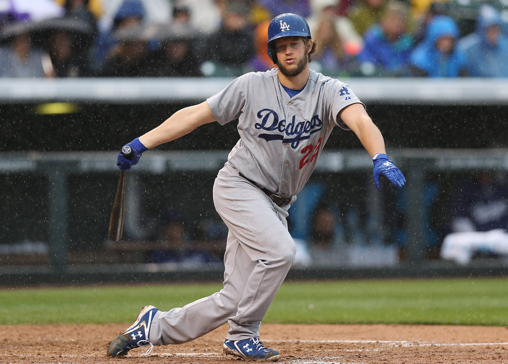 . As rain falls, Los Angeles Dodgers\' Clayton Kershaw strikes out  to end the top of the fifth inning against the Colorado Rockies in a baseball game in Denver on Sunday, June 8, 2014. (AP Photo/David Zalubowski)