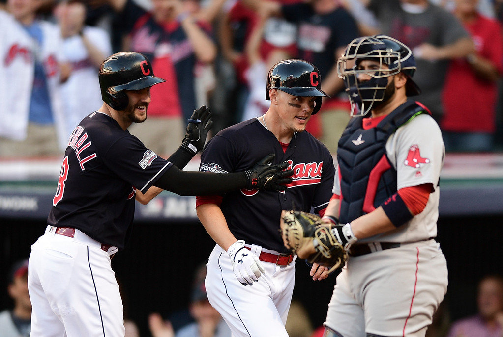 . Cleveland Indians\' Lonnie Chisenhall (8) celebrates his three-run home run with Brandon Guyer as Boston Red Sox catcher Sandy Leon looks on in the second inning during Game 2 of baseball\'s American League Division Series, Friday, Oct. 7, 2016, in Cleveland. (AP Photo/David Dermer)