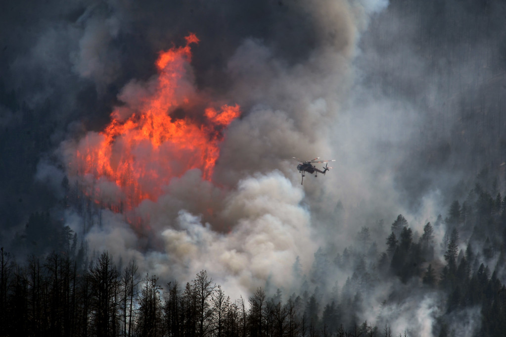 . JEFFERSON COUNTY, CO - JUNE 20:  A helicopter goes in to make a water drop as huge flames burn stands of trees on US Forest Service land on the Lime Gulch Fire off of Foxton Road near Conifer, CO on June 20, 2013.  This new fire is burning almost next to last year\'s Lower North Fork fire on June 20, 2013.  Photo by Helen H. Richardson/The Denver Post)