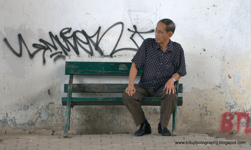 Old man on  a park bench photographed in Bangkok, Thailand in December 2009