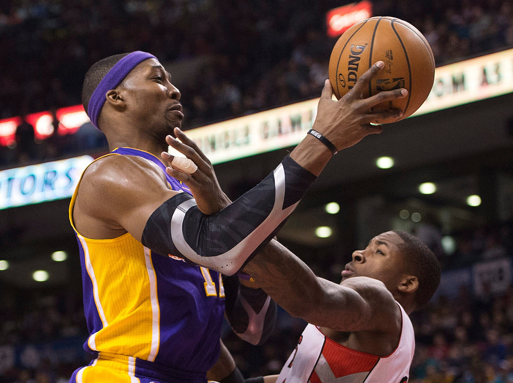 . Los Angeles Lakers forward Dwight Howard, left, drives past Toronto Raptors\' Ed Davis, right, during first half NBA basketball action in Toronto on Sunday Jan. 20, 2013. (AP Photo/THE CANADIAN PRESS,Nathan Denette)