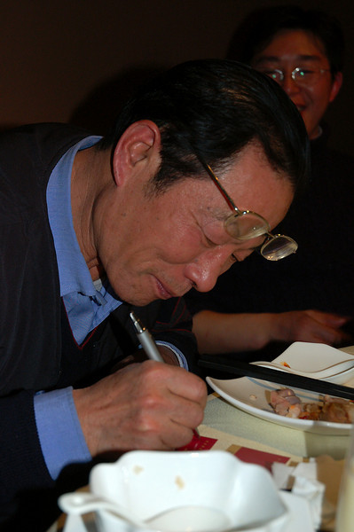 Mr Xian writing his signature