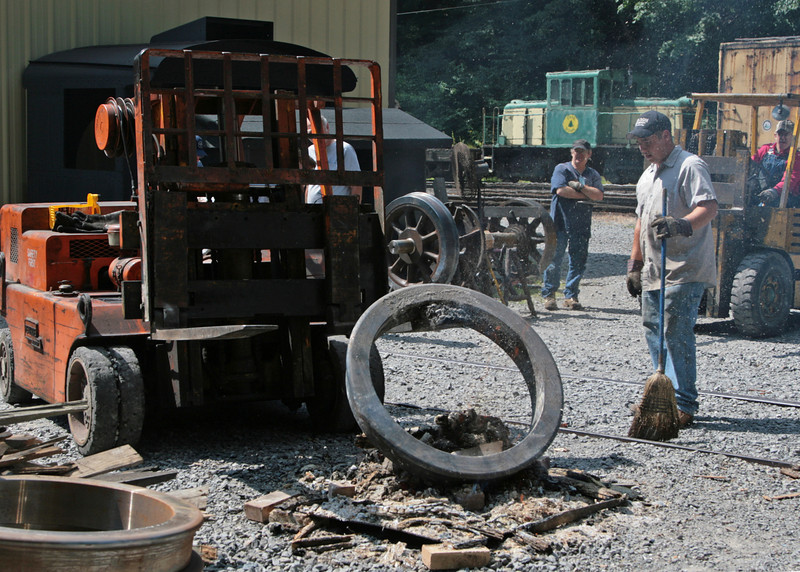 A hot tire is taken out of the fire as workers prepare to put it on the wheel.