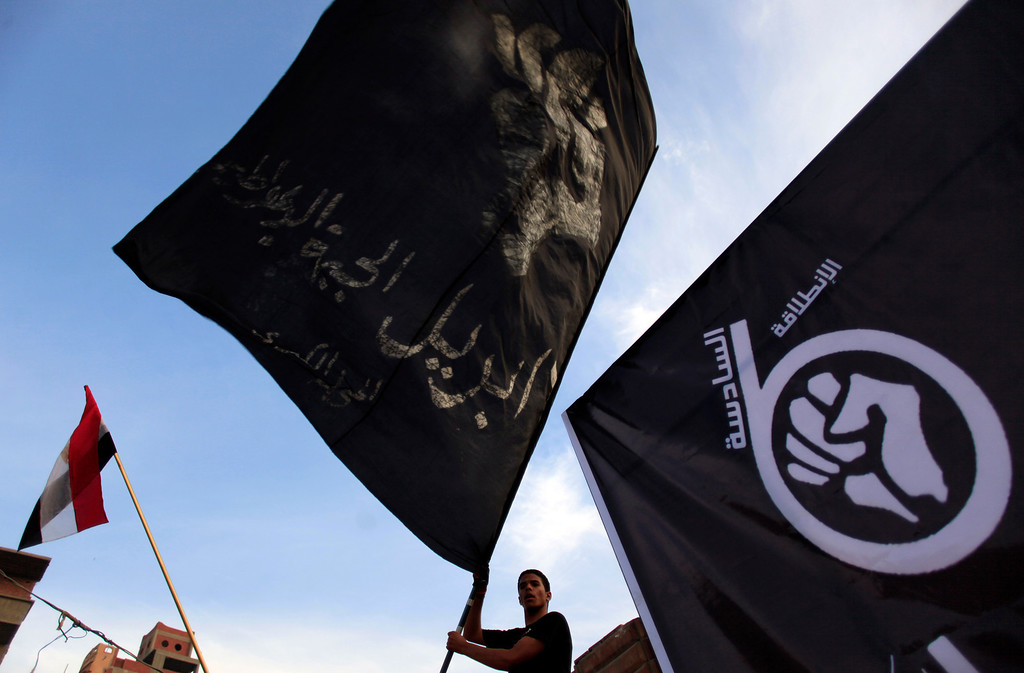 . An Egyptian protester waves a black flag during a rally of Egyptís April 6 Youth Movement in Mahalla, 125 kilometers (about 77 miles) north of Cairo, Egypt, Saturday, April 6, 2013. Thousands of activists took to the streets Saturday to mark the fifth anniversary of the founding of a leading opposition group, the April 6 Youth Movement, and to push a long list of demands on Morsi, including the formation of a more inclusive government amid a worsening economy.(AP Photo/Khalil Hamra)