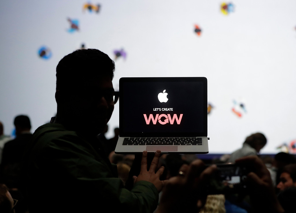 . A man holds up a laptop computer before an announcement of new products at the Apple Worldwide Developers Conference in San Jose, Calif., Monday, June 5, 2017. (AP Photo/Marcio Jose Sanchez)