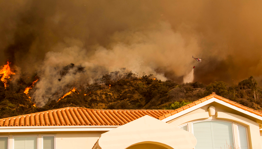 . A firefighting helicopter makes a water drop behind a home as a wildfire burns just north of the San Gabriel Valley community of Glendora, Calif., on Thursday, Jan 16, 2014. Southern California authorities have ordered the evacuation of homes at the edge of a fast-moving wildfire burning in the dangerously dry foothills of the San Gabriel Mountains. (AP Photo/Ringo H.W. Chiu)