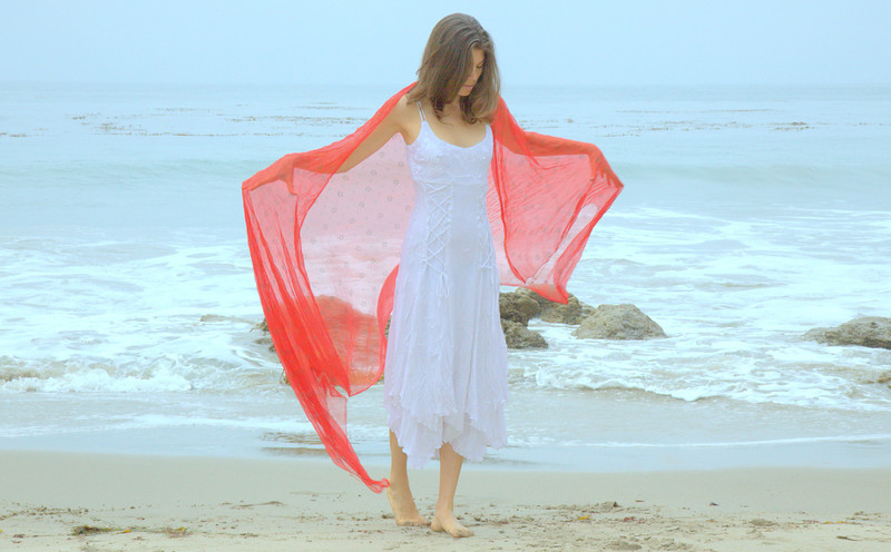 Pretty model with red scarf against ocean.