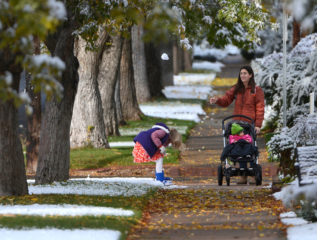 . Nanny, Nicole Ruggiano, right, playful tosses a snowball at Ellie Klebe, 7, as Ruggiano pushes Ellie\'s sister, Samantha, in a stroller while walking Ellie to school near Iliff Ave and Fillmore St. in Denver Colorado, Friday morning, October 18, 2013. (Photo By Andy Cross/The Denver Post)
