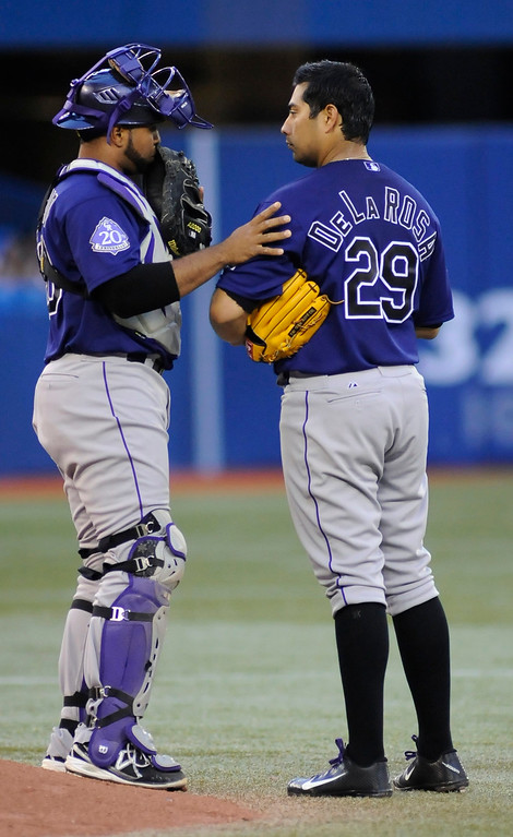 . Colorado Rockies catcher Wilin Rosario (L) talks to pitcher Jorge De La Rosa (R) during the fifth inning of their MLB American League game against the Toronto Blue Jays in Toronto June 17, 2013.   REUTERS/Jon Blacker