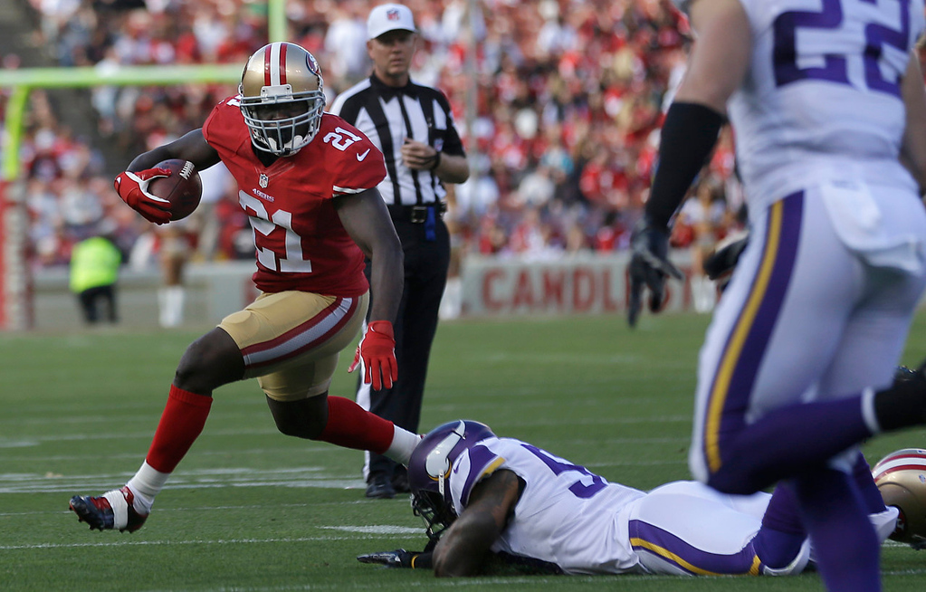 . 49ers running back Frank Gore, left, runs past prone Vikings linebacker Erin Henderson during the first quarter. (AP Photo/Marcio Jose Sanchez)