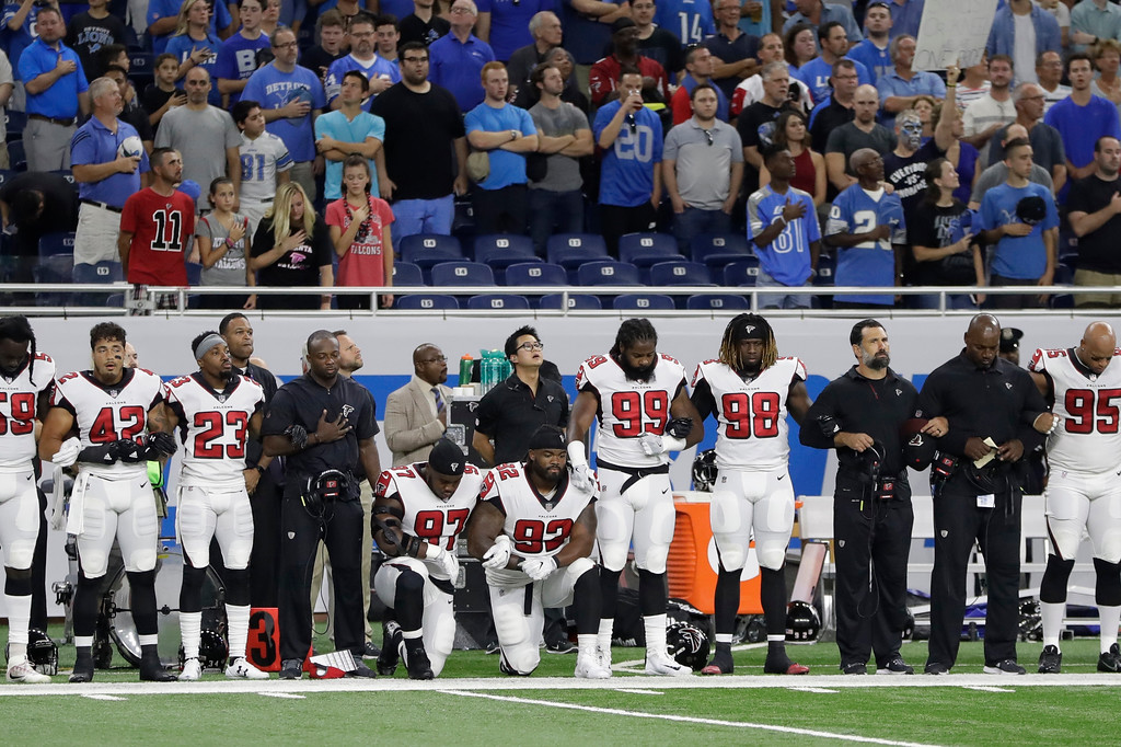 . Atlanta Falcons defensive tackles Grady Jarrett (97) and Dontari Poe (92) take a knee during the national anthem before an NFL football game, Sunday, Sept. 24, 2017, in Detroit. (AP Photo/Carlos Osorio)