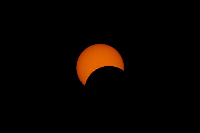 The moon makes its way over the Sun.  Notice the sunspots.
