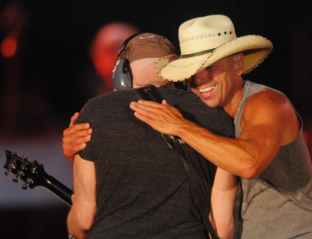. Kenney Chesney hugs a guitarist as they perform. (Pioneer Press: John Autey)