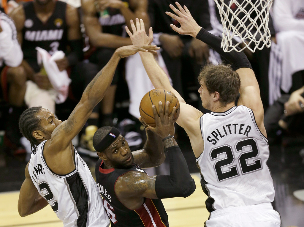 . Miami Heat\'s LeBron James looks to pass between San Antonio Spurs\' Kawhi Leonard (2) and San Antonio Spurs\' Tiago Splitter (22), of Brazil, during the first half at Game 4 of the NBA Finals basketball series, Thursday, June 13, 2013, in San Antonio. (AP Photo/David J. Phillip)