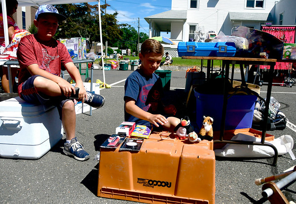 7/21/2018 Mike Orazzi | Staff Julien and Mason St. Jean sort items during the West End Flea Market held at the Immanuel Lutheran Church on West Street in Bristol Saturday morning.