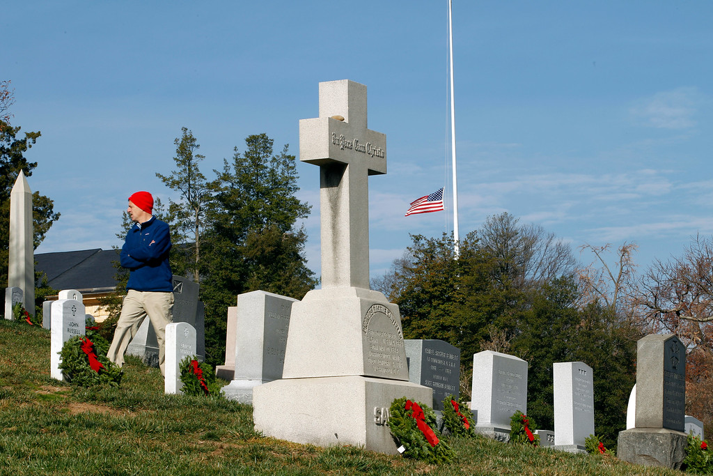 . An American flag flies a half staff as wreaths have been placed at graves at Arlington National Cemetery in Arlington, Va. on Saturday Dec. 15, 2012, during Wreaths Across America Day. (AP Photo/Jose Luis Magana)