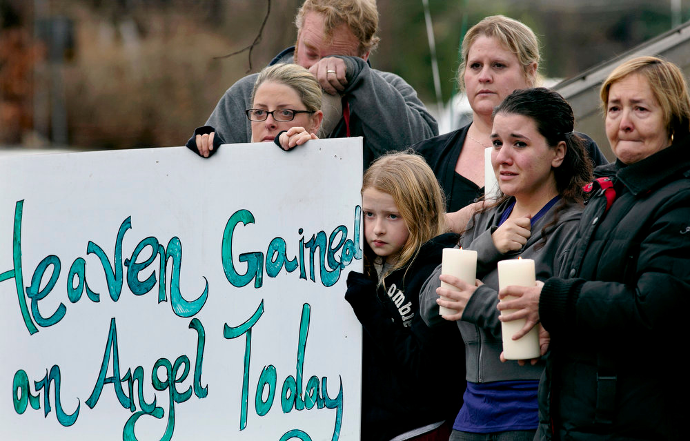 Description of . Tom Doyle, back left, standing with family and co-workers, wipes his face as the funeral procession for James Mattioli, 6, who died in the Sandy Hook Elementary School shootings, approaches the St. John's Cemetery Tuesday, Dec. 18, 2012, in Darien, Conn. Center are his wife Debbie and daughter Emily, 10. Adam Lanza opened fire Sandy Hook Elementary School in Newtown on Friday, killing 26 people, including 20 children.  (AP Photo/Craig Ruttle)