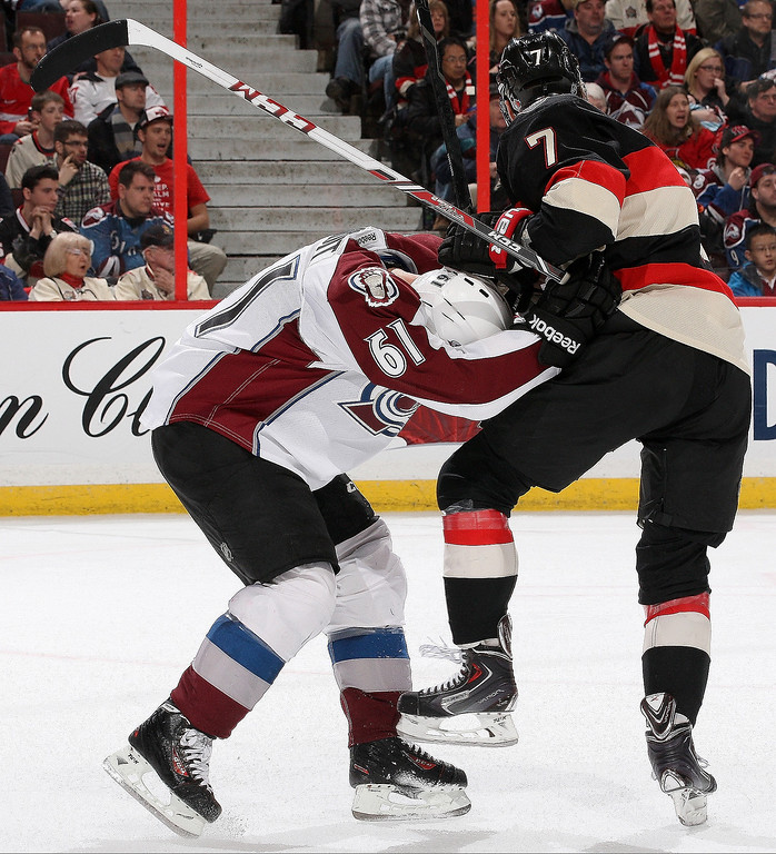 . Kyle Turris #7 of the Ottawa Senators checks Andre Benoit #61 of the Colorado Avalanche during an NHL game at Canadian Tire Centre on March 16, 2014 in Ottawa, Ontario, Canada.  (Photo by Jana Chytilova/Freestyle Photography/Getty Images)