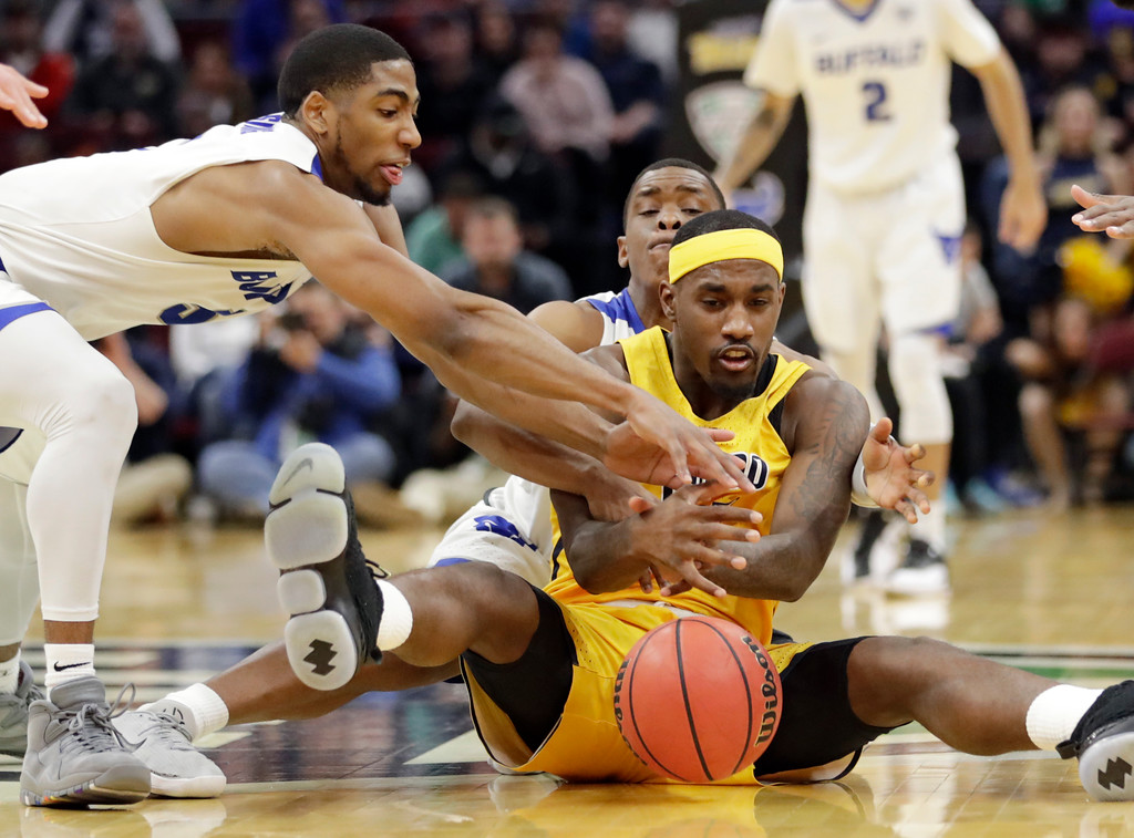 . Toledo\'s Willie Jackson, center, and Buffalo\'s CJ Massinburg, left, and Davonta Jordan, behind, battle for a loose ball during the second half of an NCAA college basketball championship game of the Mid-American Conference tournament, Saturday, March 10, 2018, in Cleveland. Buffalo won 76-66. (AP Photo/Tony Dejak)