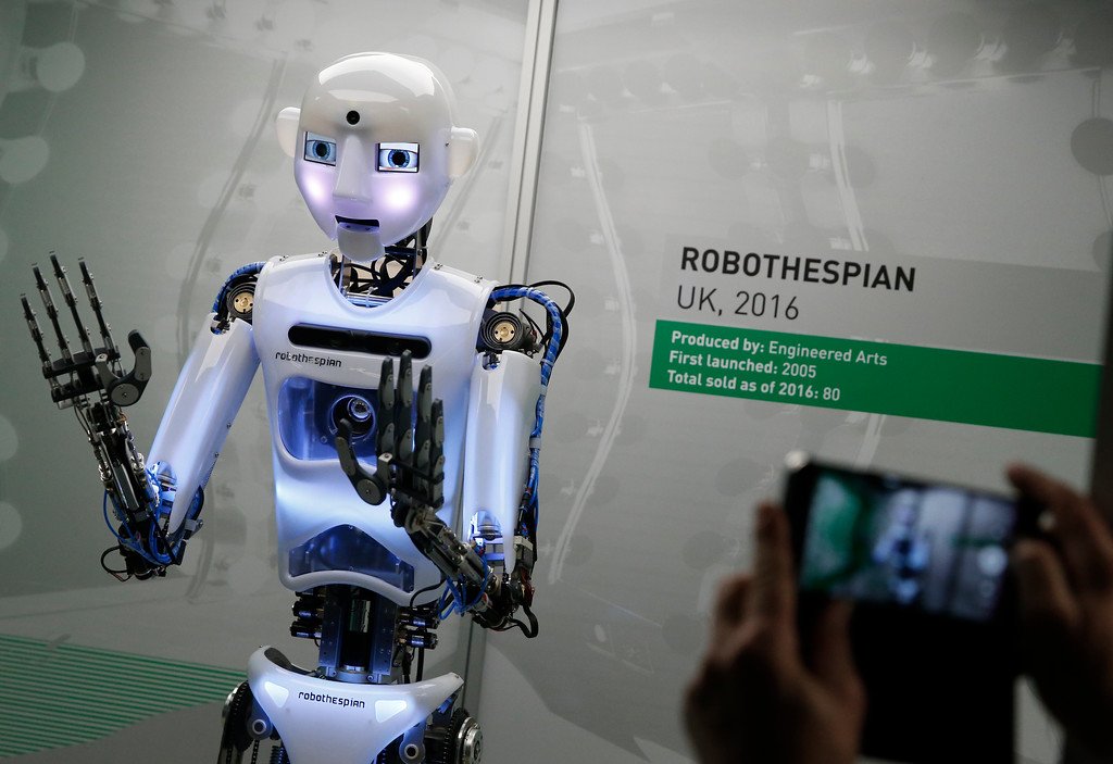 . A member of the media takes a smart phone picture of RpboThespian a British built life size robot, during a press preview for the Robots exhibition held at the Science Museum in London, Tuesday, Feb. 7, 2017. The exhibition which shows 500 years of mechanical and robotic advances is open to the public form Feb. 8 through to Sept. 3. (AP Photo/Alastair Grant)