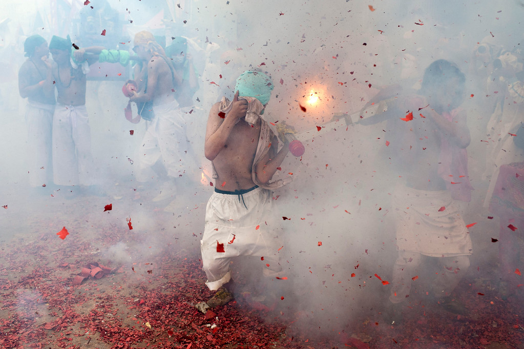 . Vegetarian festival devotees parade through the streets as firecrackers go off on September 29, 2014 in Phuket, Thailand.  (Photo by Borja Sanchez-Trillo/Getty Images)