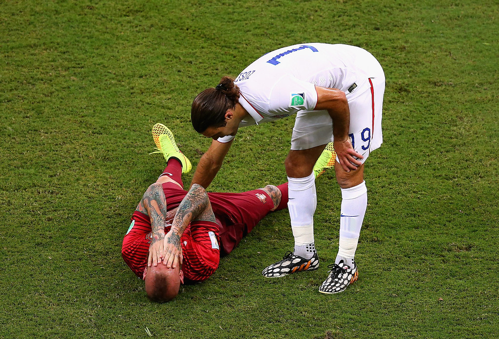 . Raul Meireles of Portugal lies on the field after a challenge as Graham Zusi of the United States looks on during the 2014 FIFA World Cup Brazil Group G match between the United States and Portugal at Arena Amazonia on June 22, 2014 in Manaus, Brazil.  (Photo by Elsa/Getty Images)