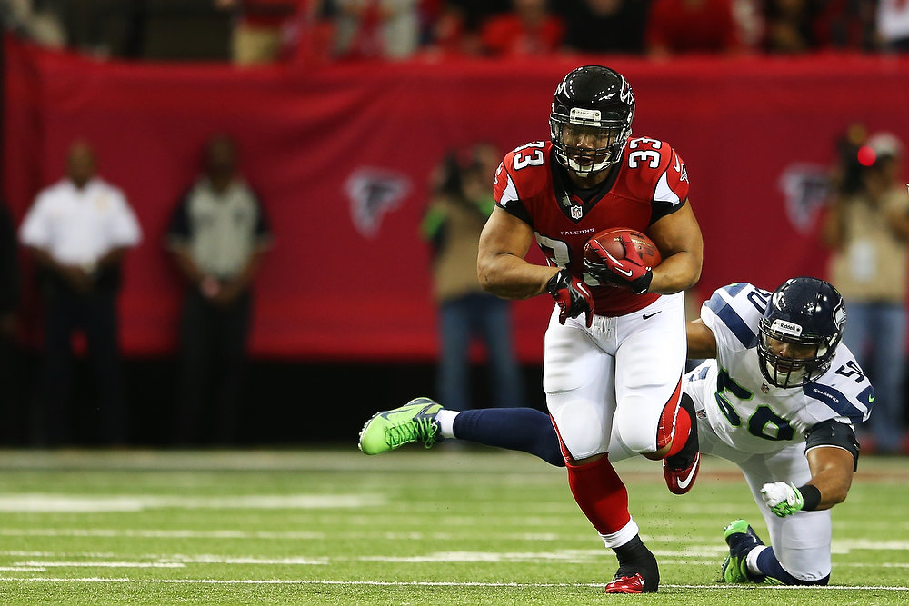 . Michael Turner #33 of the Atlanta Falcons tries to avoid the tackle of  K.J. Wright #50 of the Seattle Seahawks in the first quarter of the NFC Divisional Playoff Game at Georgia Dome on January 13, 2013 in Atlanta, Georgia.  (Photo by Mike Ehrmann/Getty Images)