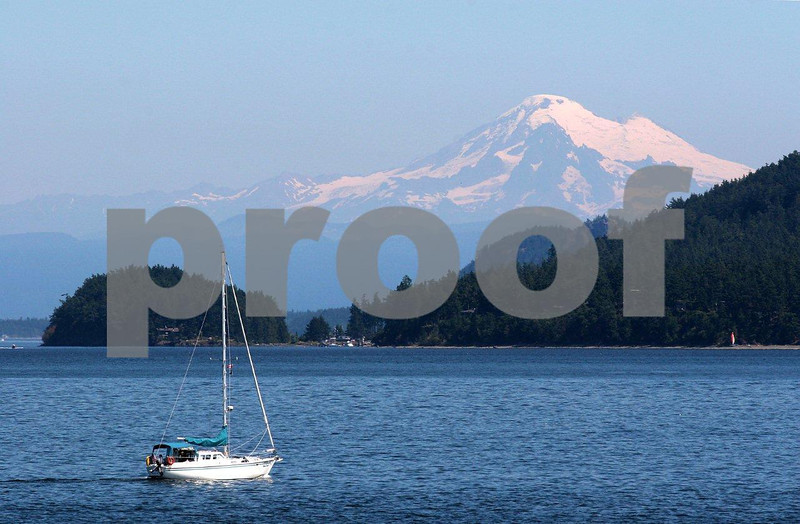 A sailboat plys the waters by Lopez Island with Mt. Baker in the background.