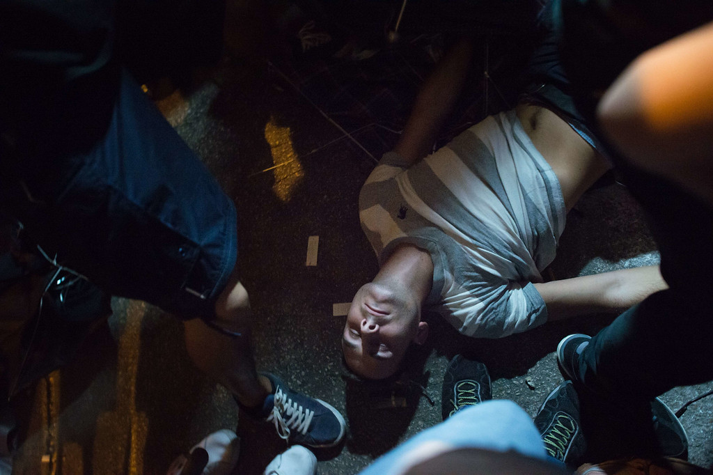 . A pro-democracy protester lies on the ground during clashes with police on a street in the Mong Kok district of Hong Kong early on October 19, 2014. Hong Kong\'s embattled government said it will open talks with student demonstrators on October 21, after three nights of violent clashes between police and protesters who have paralysed parts of the city with mass pro-democracy rallies.   AFP PHOTO / Ed JonesED JONES/AFP/Getty Images