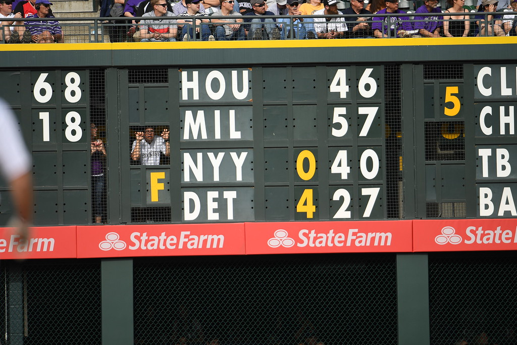 . People peak out from behind the scoreboard during the fourth inning. The Colorado Rockies played the San Diego Padres Friday, April 8, 2016 on opening day at Coors Field in Denver, Colorado. (Photo By RJ Sangosti/The Denver Post)