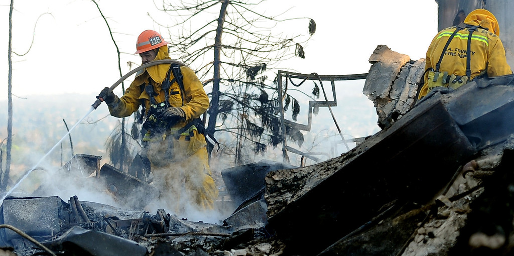 . A Los Angeles County fire capt. out of San Dimas works on the fire at the Singer Estate a top Kregmont Dr. where a guest home and six car garage burned during the Colby Fire, a 1,700-acre plus brush fire that ignited in the Angeles National Forest north of Glendora  threatening homes and prompting mandatory evacuations in Glendora, Calif., on Thursday, Jan. 16, 2014. (Keith Birmingham Pasadena Star-News)