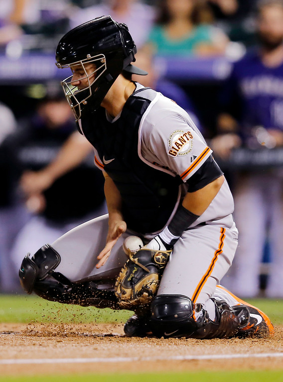 . San Francisco Giants catcher Andrew Susac bobbles the ball allowing Colorado Rockies\' Drew Stubbs to score during the fifth inning of a baseball game Tuesday, Sept. 2, 2014, in Denver. (AP Photo/Jack Dempsey)