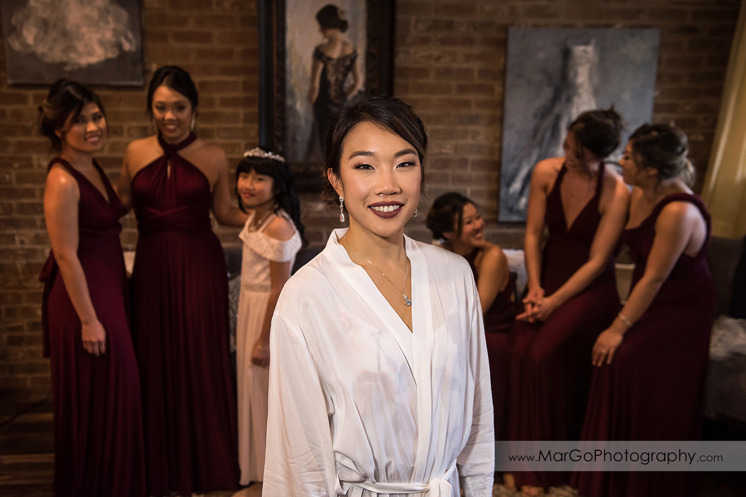 bride in white robe with bridesmaids in the background at Sunol's Casa Bella bridal suite
