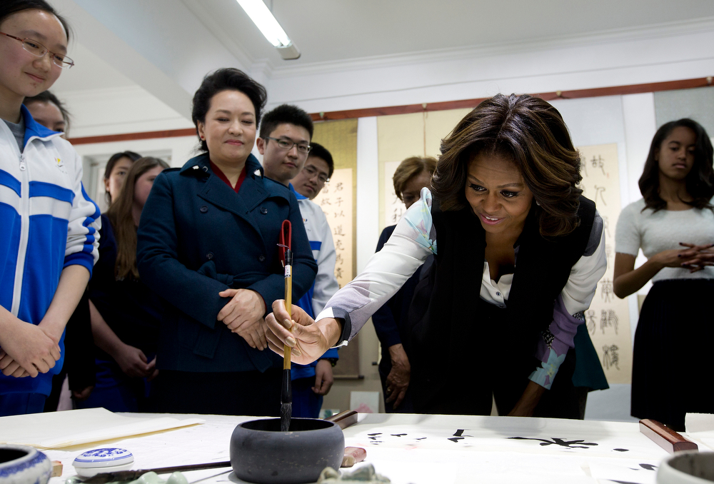 . U.S. First Lady Michelle Obama dip a brush in an ink pod as she tries out writing Chinese characters as Peng Liyuan, wife of Chinese President Xi Jinping, left, watches her during their visit in a Chinese traditional calligraphy class at the Beijing Normal School, a school that prepares students to go abroad in Beijing, China Friday, March 21, 2014. (AP Photo/Andy Wong, Pool)