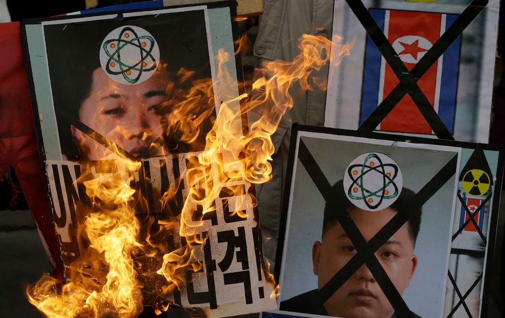 Description of . South Korean protesters burn the pictures of North Korean leader Kim Jong Un during an anti-North Korea rally following a nuclear test conducted by North Korea, in Seoul, South Korea, Tuesday, Feb. 12, 2013. North Korea said it successfully detonated a miniaturized nuclear device at a northeastern test site Tuesday, defying U.N. Security Council orders to shut down atomic activity or face more sanctions and international isolation. (AP Photo/Lee Jin-man)