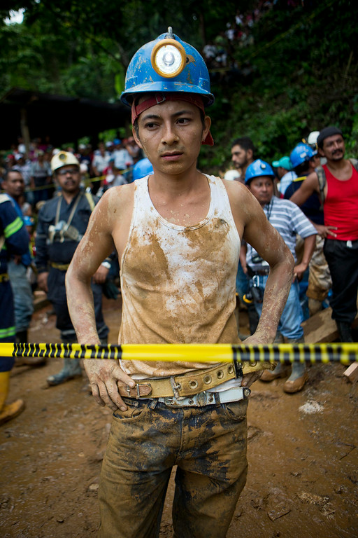 . A miner takes a break from the rescue operations at El Comal gold and silver mine after a landslide trapped at least 24 miners inside, in Bonanza, Nicaragua, Friday, Aug. 29, 2014. Rescuers on Friday located 20 of at least 24 gold miners trapped by a landslide in northern Nicaragua, but were not immediately able to bring them to safety. (AP Photo/Esteban Felix)