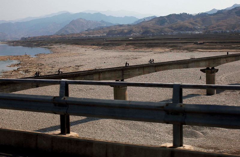 . People walk and use bicycles to cross a railroad bridge over a riverbed north of Pyongyang, North Korea on April 19, 2011.  (AP Photo/David Guttenfelder)