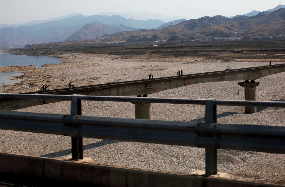 Description of . People walk and use bicycles to cross a railroad bridge over a riverbed north of Pyongyang, North Korea on April 19, 2011.  (AP Photo/David Guttenfelder)