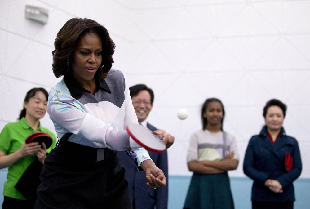 . US First Lady Michelle Obama plays table tennis as Peng Liyuan (R), wife of Chinese President Xi Jinping, looks on during their visit to the Beijing Normal School, a school that prepares students to attend university abroad in Beijing on March 21, 2014.  Michelle Obama arrived in Beijing with her mother and daughters to kick off a seven-day, three-city tour where she will focus on education and cultural exchange. (ANDY WONG/AFP/Getty Images)