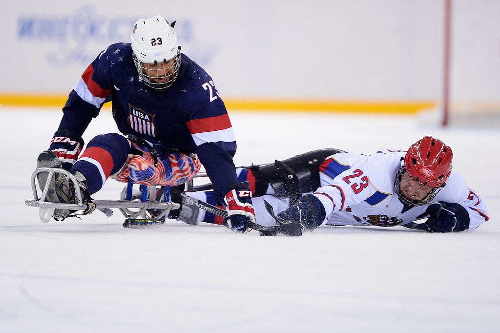 . Rico Roman of the United States and Ilia Volkov of Russia battle for the puck during the Ice Sledge Hockey Preliminary Round Group B match between the United States of America and Russia during day four of Sochi 2014 Paralympic Winter Games at Shayba Arena on March 11, 2014 in Sochi, Russia.  (Photo by Dennis Grombkowski/Getty Images)