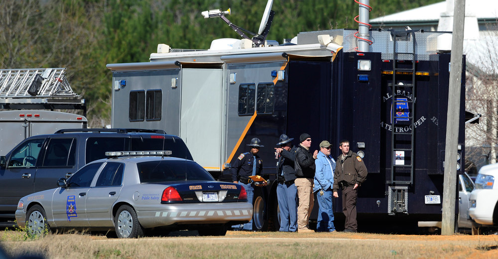 . Law officers stand beside the Alabama State trooper mobile command post at the Dale County hostage scene in Midland City, Ala. on Thursday, Jan. 31, 2013. A gunman holed up in a bunker with a 6-year-old hostage has kept law officers at bay since the standoff began when he killed a school bus driver and dragged the boy away, authorities said. (AP Photo/Montgomery Advertiser, Mickey Welsh)
