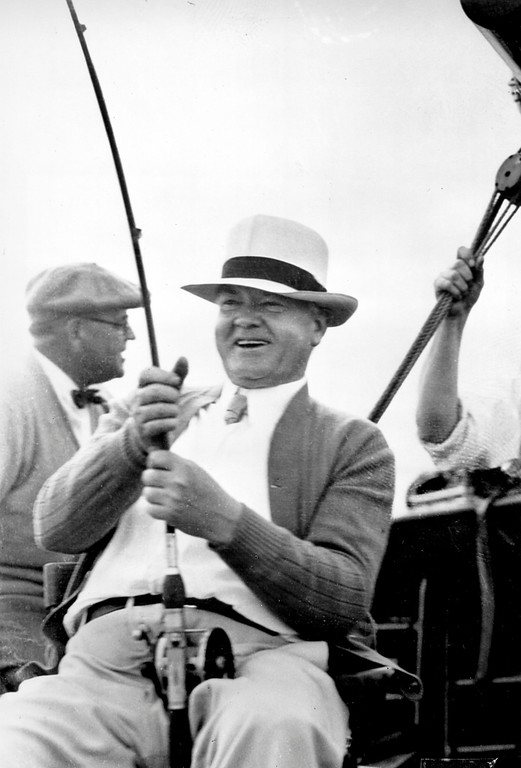 . ** HOLD FOR RELEASE UNTIL 12:01 A.M. EDT TUESDAY, AUG. 18  - FOR USE WITH PRESIDENTIAL VACATIONS STORY *8 FILE - In this Jan. 21, 1933, file photo, U.S. President Herbert C. Hoover laughs as he spears one of the five large Sailfish he caught on his vacation trip aboard the Sequoia in Florida waters. The photograph was taken by the president\'s secretary, Lawrence Richey.  (AP Photo/File)